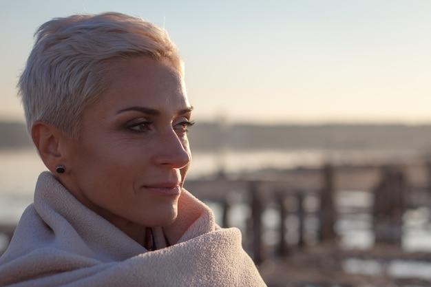 Erwachsene blondine von mittlerem alter wickelten sich in einem hellen plaid auf dem strand ein