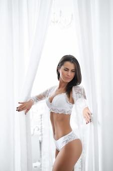 Erwachsene brünette frau in sexy weißen dessous