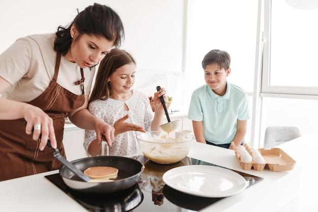 Erwachsene brünette frau und glückliche kinder, die zusammen kochen und pfannkuchen auf modernem herd in der küche zu hause braten