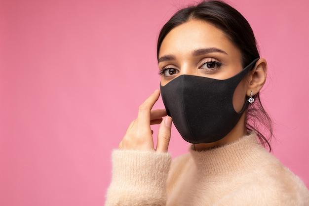 Erwachsene charmante frau in wiederverwendbarer schwarzer virenschutzmaske im gesicht gegen coronavirus einzeln auf der rosafarbenen hintergrundwand.