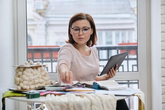Erwachsene designerin, die mit stoffmustern arbeitet