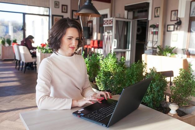Erwachsene elegante geschäftsfrau im weißen kleid, das mit laptop im café sitzt. schöne brünette dame mit notizbuch im café. schuss einer frau mittleren alters, die auf der tastatur tippt