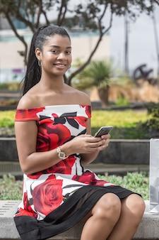 Erwachsene ethnische zufriedene frau, die smartphone im park verwendet