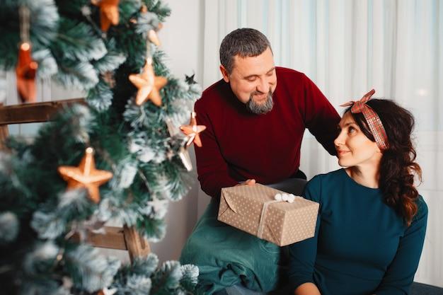 Erwachsene familie, die zu hause nahe weihnachtsbaum sitzt