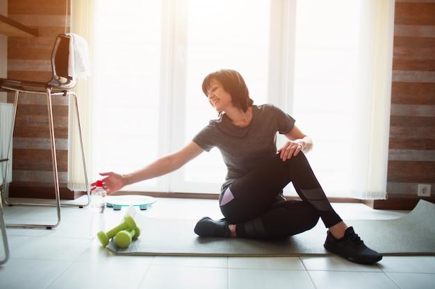 Erwachsene fit schlanke frau hat training zu hause. älteres weibliches modell, das wasserflasche mit lächeln erreicht. setzen sie sich während der trainingspause auf eine yogamatte. alleine im raum trainieren.