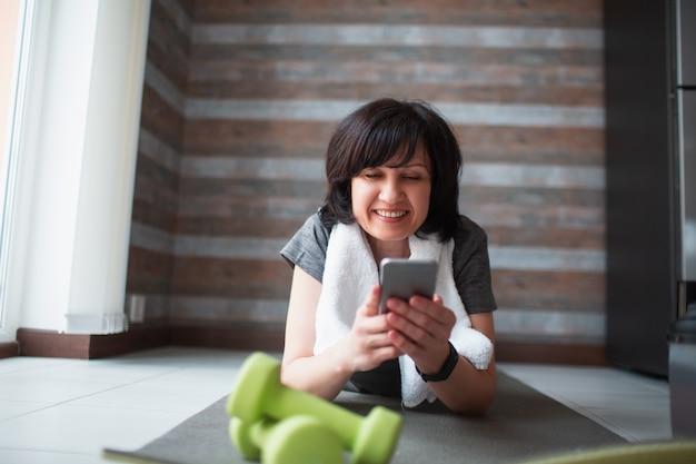 Erwachsene fit schlanke frau hat training zu hause. auf der matte liegen und smartphone benutzen. surfen im internet während der trainingspause. starke mächtige reife frau auf bild während der pause.