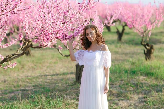 Erwachsene frau 35 jahre alt in einem garten mit rosa blühenden bäumen