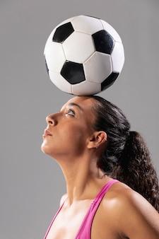 Erwachsene frau der nahaufnahme, die ball auf kopf hält