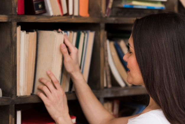 Erwachsene frau der nahaufnahme, die nach romanen sucht