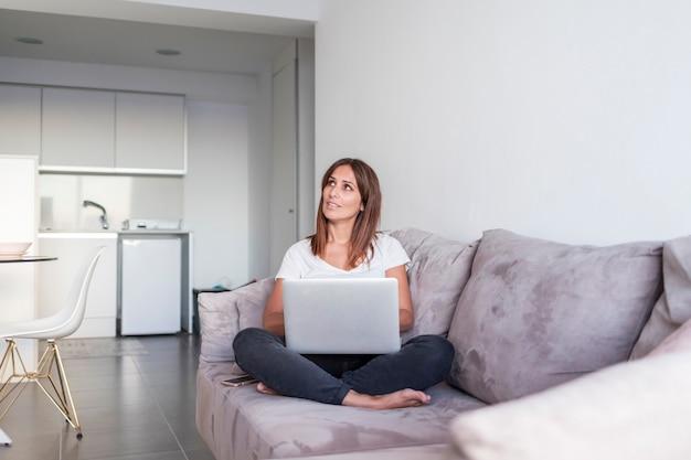 Erwachsene frau, die auf einem sofa sitzt, während laptop und tasse tee hält