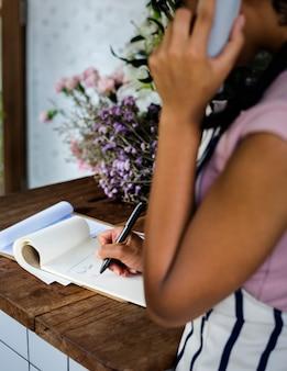 Erwachsene frau, die auftrags-anruf im flora shop empfängt