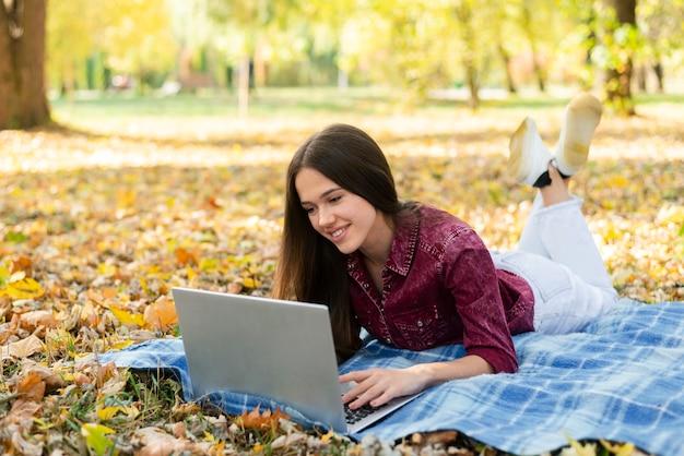 Erwachsene frau, die draußen an laptop arbeitet
