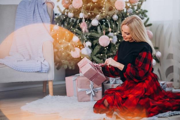Erwachsene frau, die durch weihnachtsbaum sitzt und geschenk hält