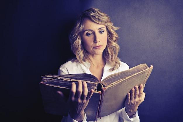 Erwachsene frau, die einen kodex liest