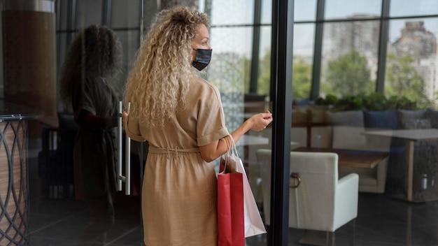 Erwachsene frau, die einkaufstaschen am einkaufszentrum trägt