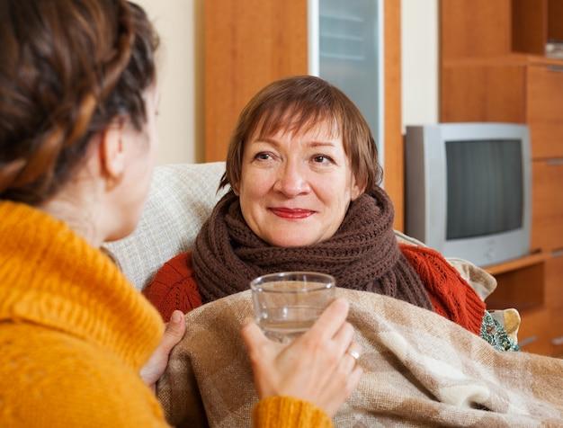 Erwachsene frau, die für unwohl ältere mutter sich interessiert