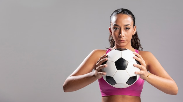 Erwachsene frau, die fußball hält