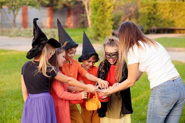 Erwachsene frau, die glücklichen kindern in halloween-kostümen während des süßes oder saures-ereignisses im park süßigkeiten gibt
