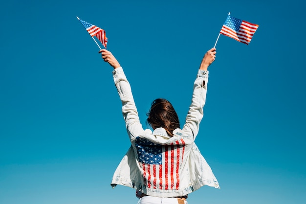 Erwachsene frau, die hände mit amerikanischen flaggen anhebt