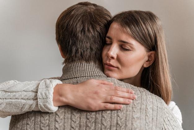 Erwachsene frau, die ihren ehemann umarmt