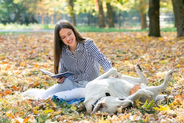 Erwachsene frau, die ihren hund im park streichelt