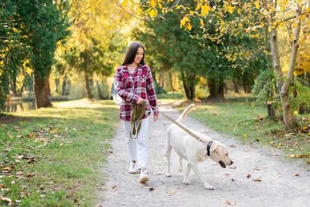 Erwachsene frau, die in den park mit ihrem hund geht