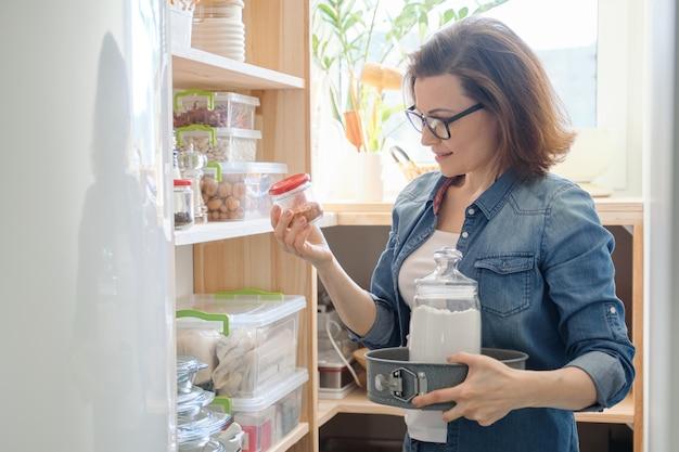 Erwachsene frau, die küchengeschirr und lebensmittel aus den regalen nimmt