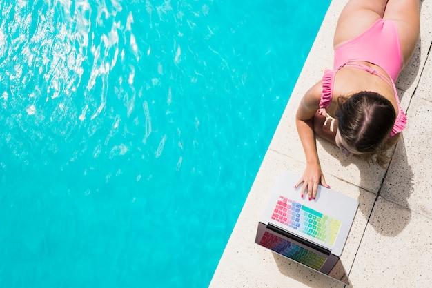 Erwachsene frau, die laptop nahe swimmingpool verwendet