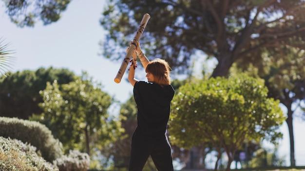 Erwachsene frau, die mit bambusstock trainiert