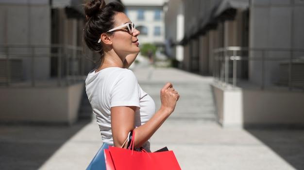 Erwachsene frau, die mit einkaufstüten aufwirft