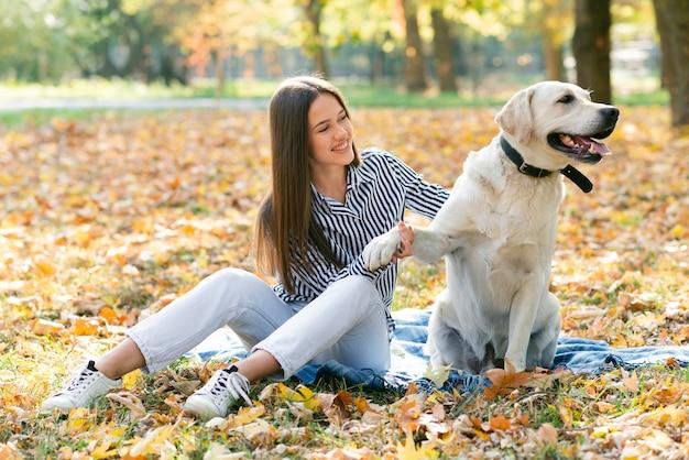Erwachsene frau, die mit ihrem hund im park spielt