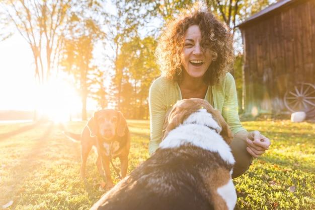 Erwachsene frau, die mit ihren hunden am park spielt