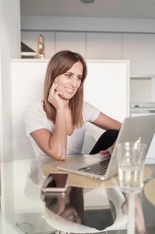 Erwachsene frau, die mit laptop zu hause arbeitet