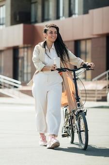 Erwachsene frau, die mit umweltfreundlichem fahrrad aufwirft