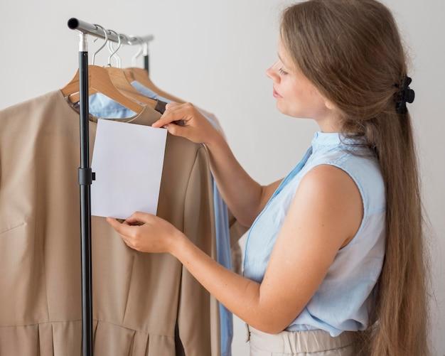 Erwachsene frau, die neue kleidung zu hause überprüft