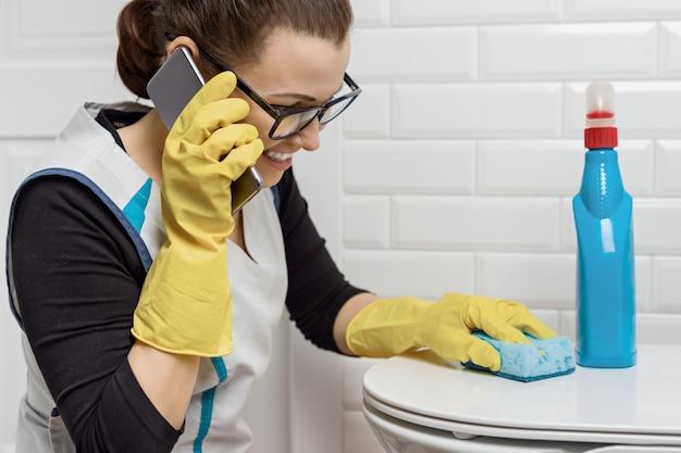 Erwachsene frau, die reinigung mit reinigungsmitteln beim sprechen mit smartphone tut