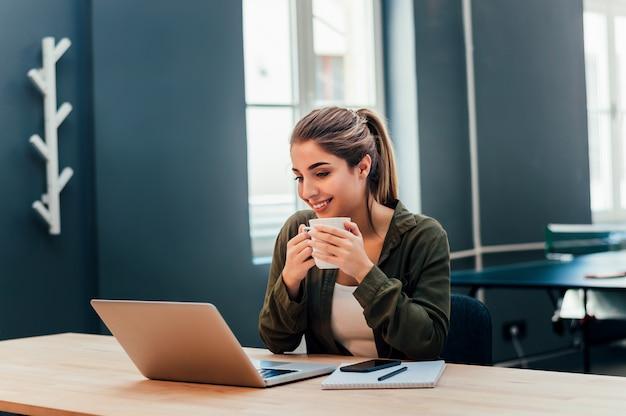 Erwachsene frau, die schale hält und beim betrachten ihrer laptop-computers beim sitzen nahe fenster lacht.