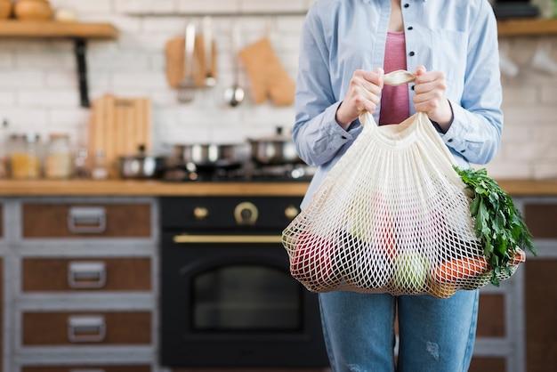 Erwachsene frau, die wiederverwendbaren beutel mit bio-gemüse hält