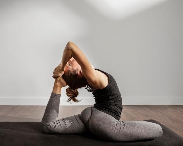Erwachsene frau, die yoga zu hause macht