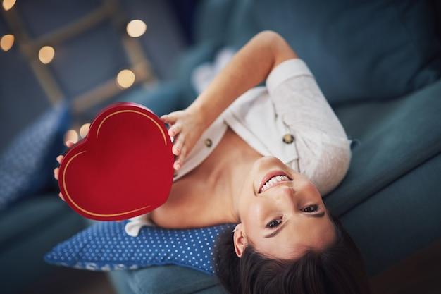 Erwachsene frau, die zu hause geschenk hält, valentinsgrußkonzept
