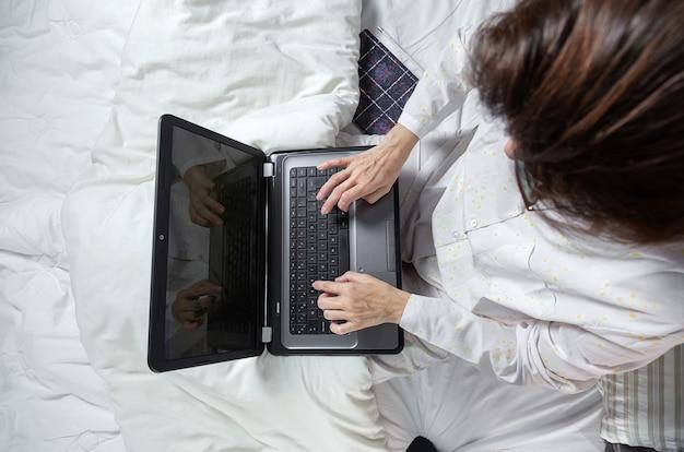 Erwachsene frau, die zu hause im pijama arbeitet