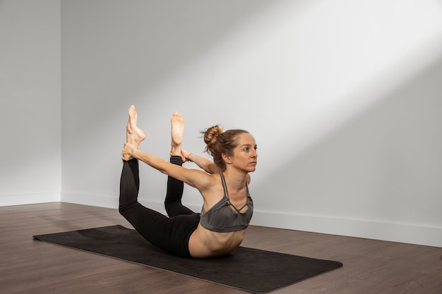 Erwachsene frau, die zu hause yoga praktiziert