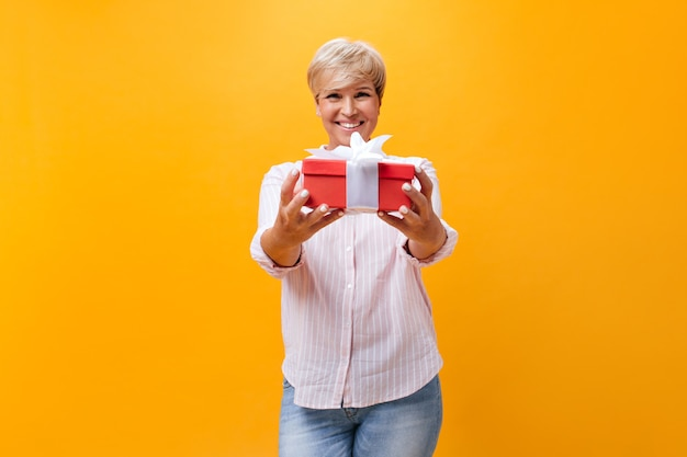 Erwachsene frau im rosa outfit, die rote geschenkbox hält