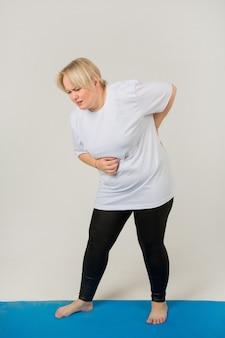 Erwachsene frau in einem weißen t-shirt, das rückenschmerzen hat