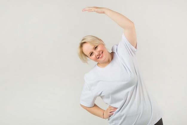 Erwachsene frau in einem weißen t-shirt, das sport treibt