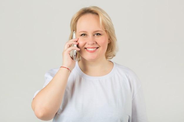 Erwachsene frau in einem weißen t-shirt mit einem telefon
