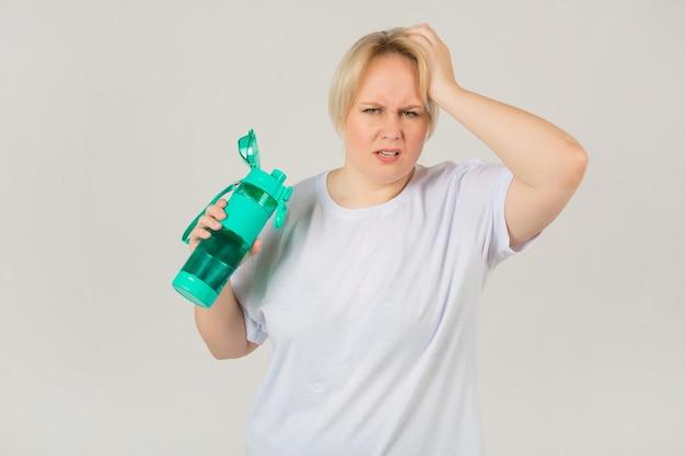 Erwachsene frau in einem weißen t-shirt mit einem wasserschüttler