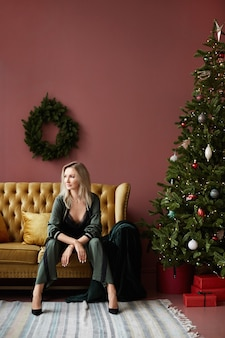 Erwachsene frau in gemütlichen hauskleidung sitzt auf der couch in der nähe des weihnachtsbaumes