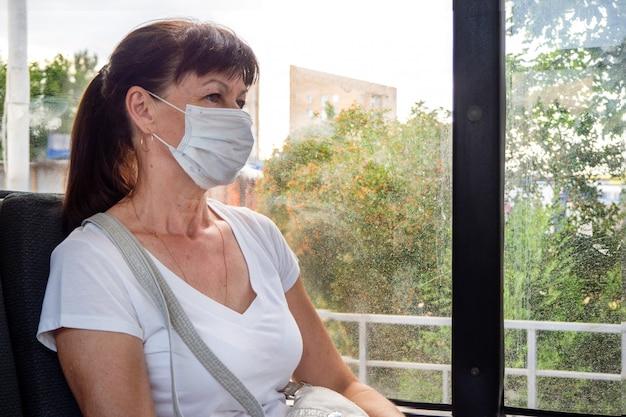 Erwachsene frau in schutzmaske reitet allein in den öffentlichen verkehrsmitteln in der stadt leer. soziale distanz. buspassagiere