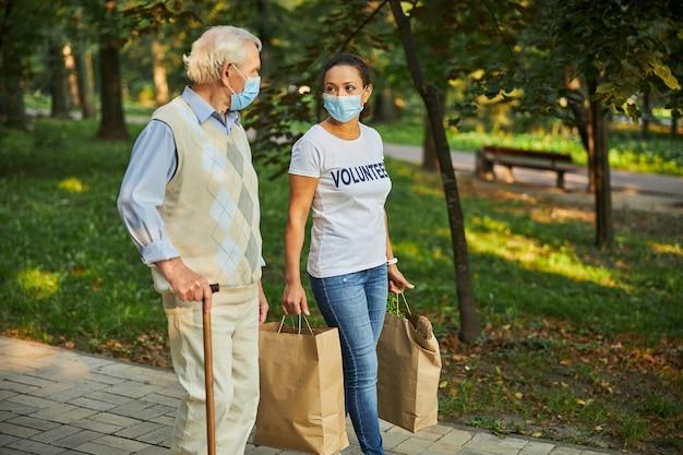 Erwachsene frau mit attraktivem alten mann, der durch den park oder wald geht